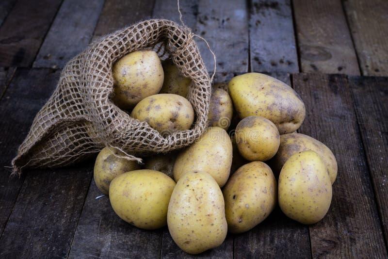 Νόστιμες πατάτες σε έναν ξύλινο πίνακα Λαχανικά στην κουζίνα tabl στοκ φωτογραφία