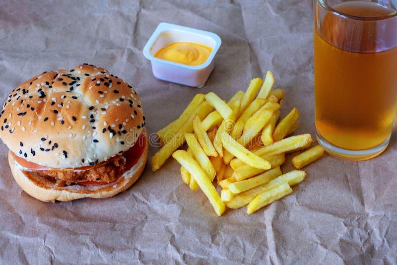 Νόστιμες χάμπουργκερ και τηγανιτές πατάτες σε ένα ξύλινο επιτραπέζιο υπόβαθρο Έννοια άχρηστου φαγητού στοκ εικόνα με δικαίωμα ελεύθερης χρήσης