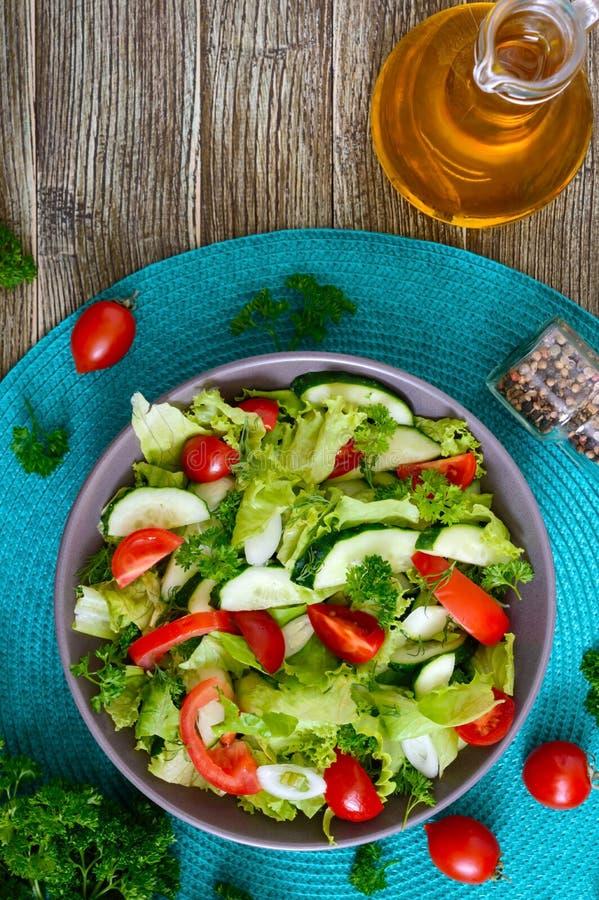 Νόστιμη διαιτητική σαλάτα βιταμινών με τα φρέσκα αγγούρια, ντομάτες, πράσινα Σαλάτα από τα οργανικά λαχανικά r στοκ εικόνα με δικαίωμα ελεύθερης χρήσης
