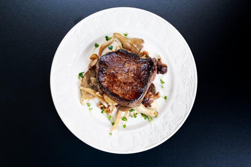 Νόστιμη μπριζόλα Mignon βόειου κρέατος με τα μανιτάρια και τα χορτάρια στο πιάτο στοκ φωτογραφία με δικαίωμα ελεύθερης χρήσης
