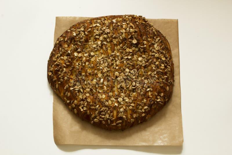 Νόστιμη ολόκληρη πίτα σε χαρτί περγαμηνής με τα σιτάρια και σπόροι στη στοκ εικόνες με δικαίωμα ελεύθερης χρήσης
