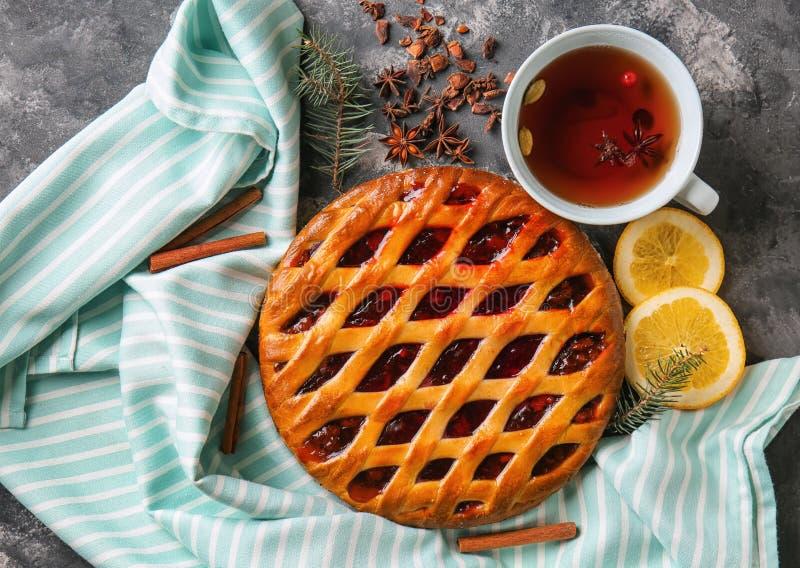 Νόστιμη πίτα Χριστουγέννων που γεμίζεται με τα τα βακκίνια και το φλυτζάνι του τσαγιού στον πίνακα στοκ φωτογραφία με δικαίωμα ελεύθερης χρήσης
