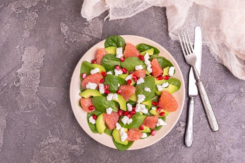 Νόστιμη σαλάτα με το γκρέιπφρουτ, το σπανάκι, φέτα, το αβοκάντο και το ρόδι στοκ φωτογραφία