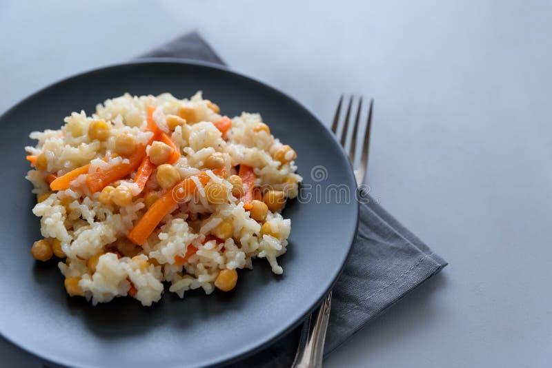 Νόστιμος χορτοφάγος pilaf με το ρύζι, το καρότο και chickpeas στο γκρίζο ξύλινο υπόβαθρο διάστημα αντιγράφων Τοπ όψη Εκλεκτική εσ στοκ φωτογραφίες