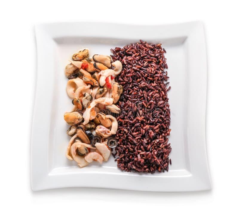 Νόστιμο βρασμένο άγριο ρύζι με τα θαλασσινά στο πιάτο, που απομονώνεται στο λευκό στοκ φωτογραφίες