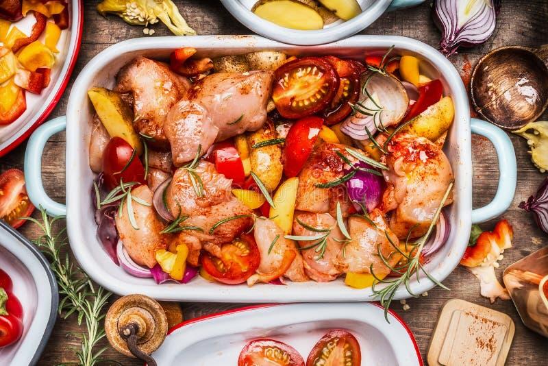 Νόστιμο κοτόπουλο με τα ζωηρόχρωμα λαχανικά και κόκκινη γλυκιά πάπρικα casserole, προετοιμασία στο αγροτικό ξύλινο υπόβαθρο με τα στοκ φωτογραφίες