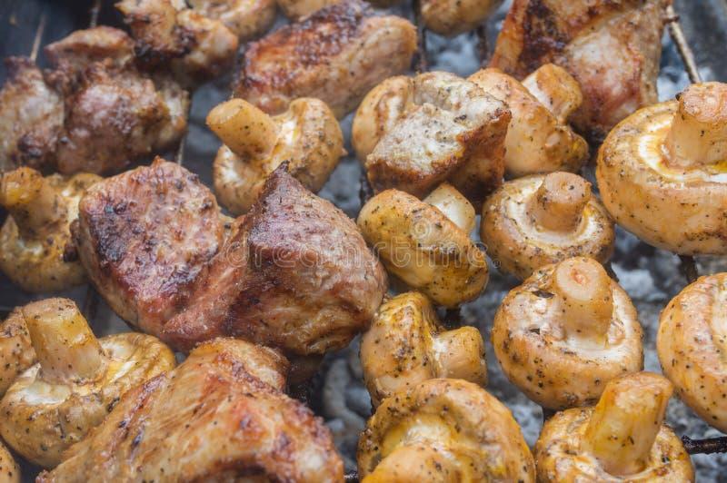Νόστιμο μαγείρεμα κρέατος χοιρινού κρέατος με τα μανιτάρια τομέων υπαίθρια στους σιγοκαίγοντας άνθρακες στοκ φωτογραφία με δικαίωμα ελεύθερης χρήσης