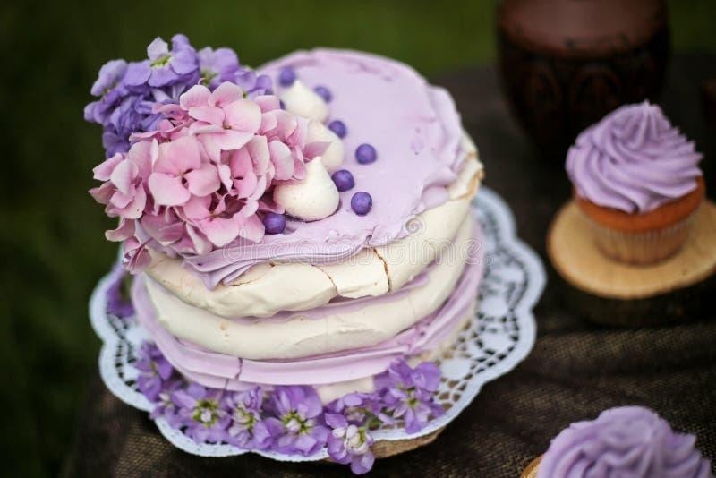 Νόστιμο πορφυρό γαμήλιο κέικ με τα λουλούδια στοκ εικόνα με δικαίωμα ελεύθερης χρήσης