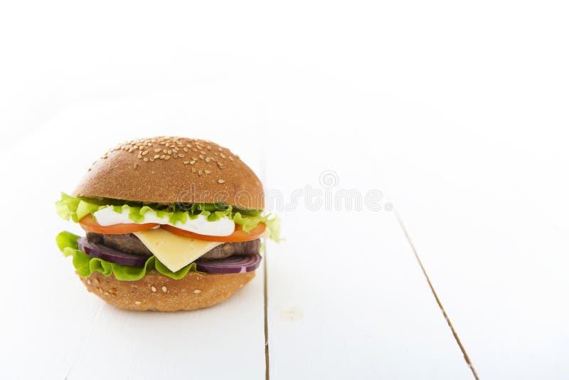 Νόστιμο χάμπουργκερ στον ξύλινο πίνακα στοκ φωτογραφία με δικαίωμα ελεύθερης χρήσης