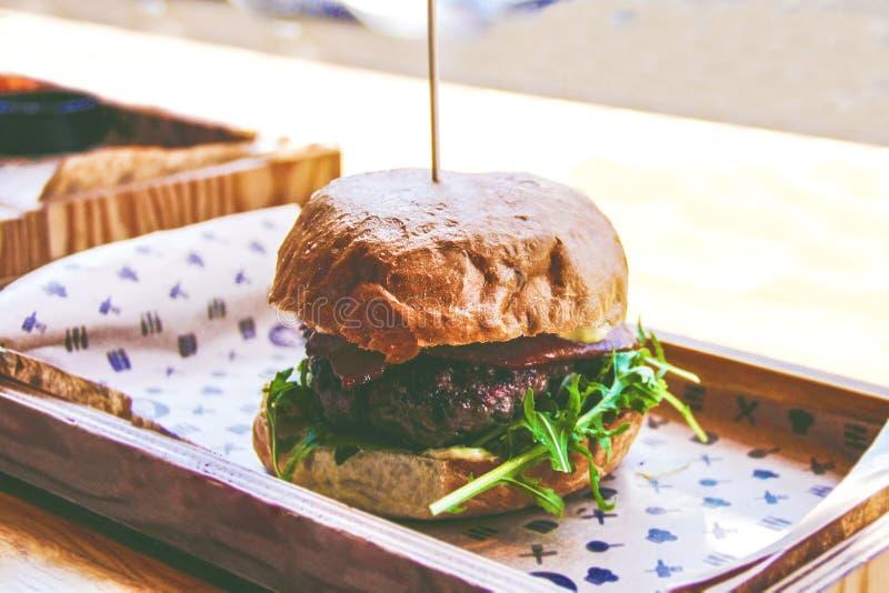 Νόστιμο burger στον ξύλινο πίνακα στοκ εικόνες