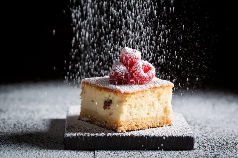 Νόστιμο cheesecake με τα σμέουρα και την κονιοποιημένη ζάχαρη στοκ φωτογραφία