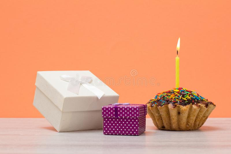 Νόστιμο muffin γενεθλίων με το κάψιμο των εορταστικών κιβωτίων κεριών και δώρων στο υπόβαθρο ροδάκινων στοκ φωτογραφία