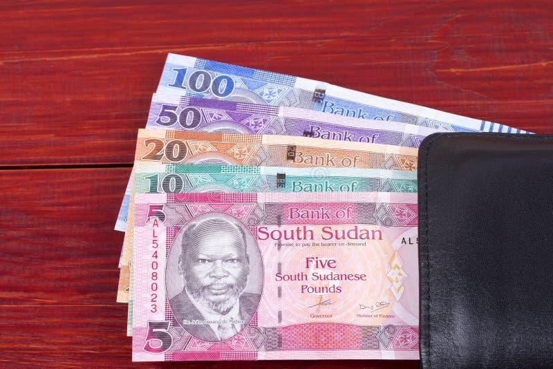 Νότια σουδανέζικα χρήματα στο μαύρο πορτοφόλι στοκ φωτογραφία
