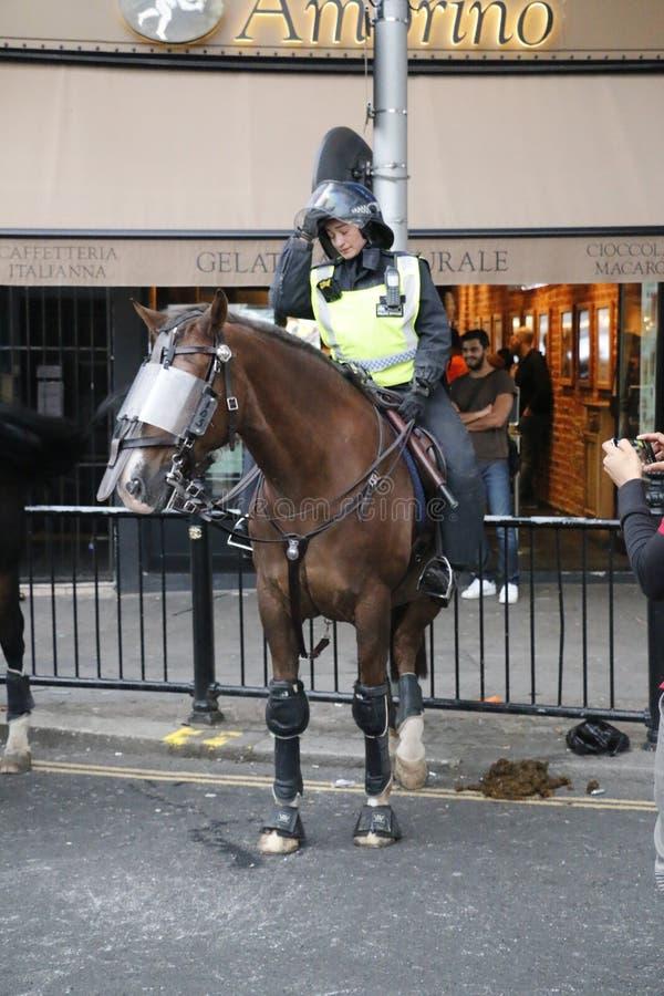 ΝΌΤΙΝΓΚ ΧΙΛ, ΛΟΝΔΙΝΟ - 27 ΑΥΓΟΎΣΤΟΥ 2018: Ο τοποθετημένος αστυνομικός ταραχής στην πλάτη αλόγου φαίνεται εξαντλημένος στο τέλος τ στοκ εικόνες
