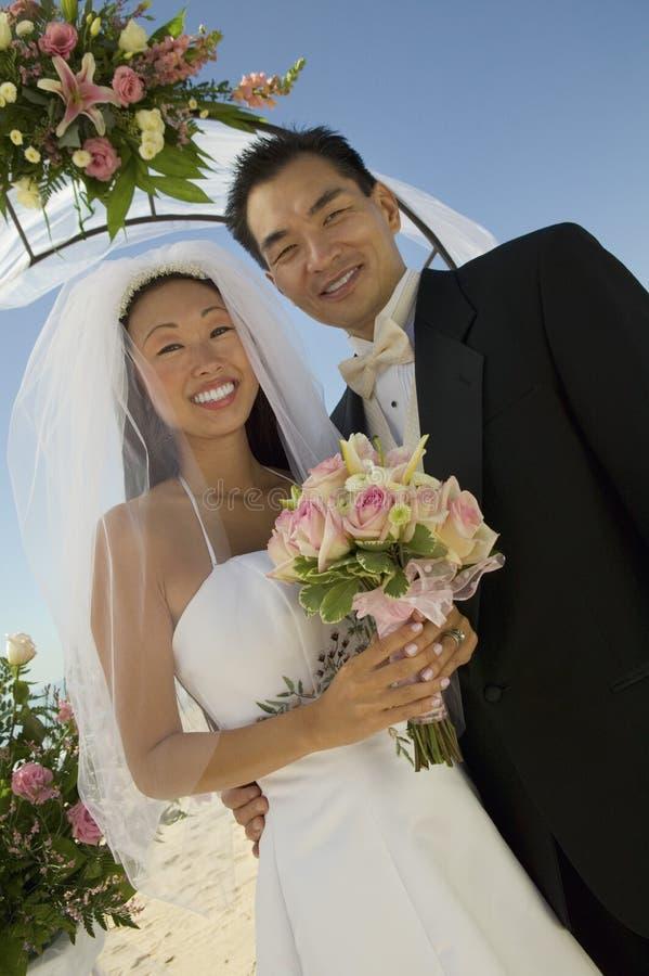 Νύφη και νεόνυμφος κάτω από την αψίδα στοκ εικόνες