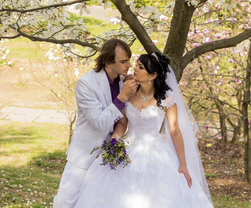 Νύφη και νεόνυμφος με μια ανθοδέσμη των φιλιών στοκ φωτογραφία