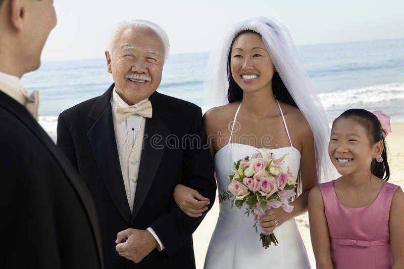 Νύφη και νεόνυμφος με την οικογένεια στον ωκεανό στοκ εικόνες