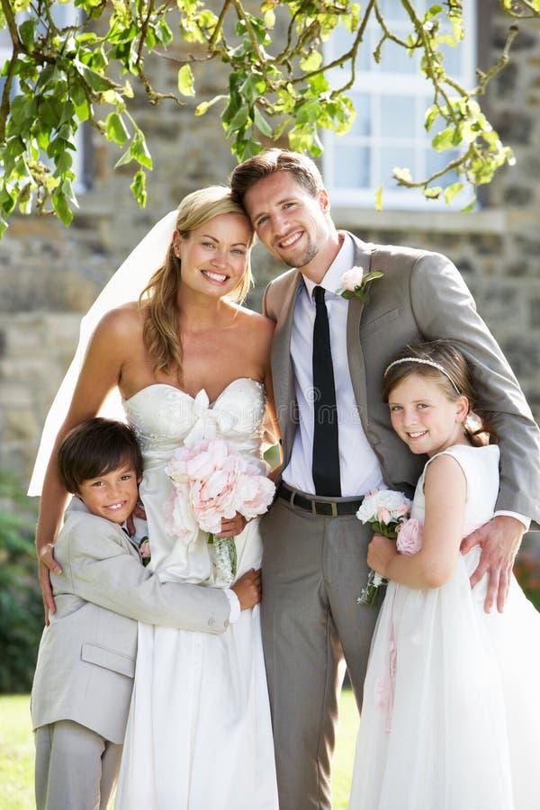 Νύφη και νεόνυμφος με την παράνυμφο και το αγόρι σελίδων στο γάμο στοκ εικόνα