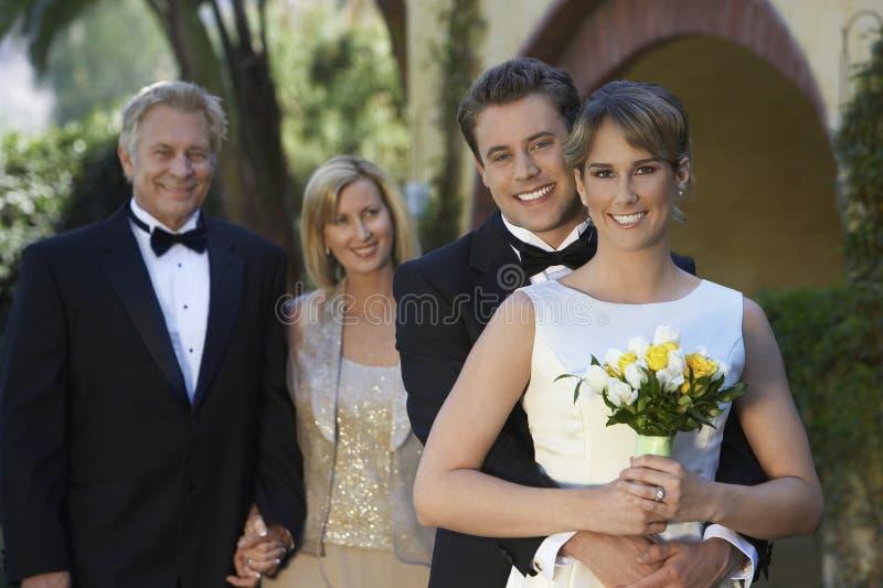 Νύφη και νεόνυμφος με τους γονείς στο υπόβαθρο στοκ εικόνες