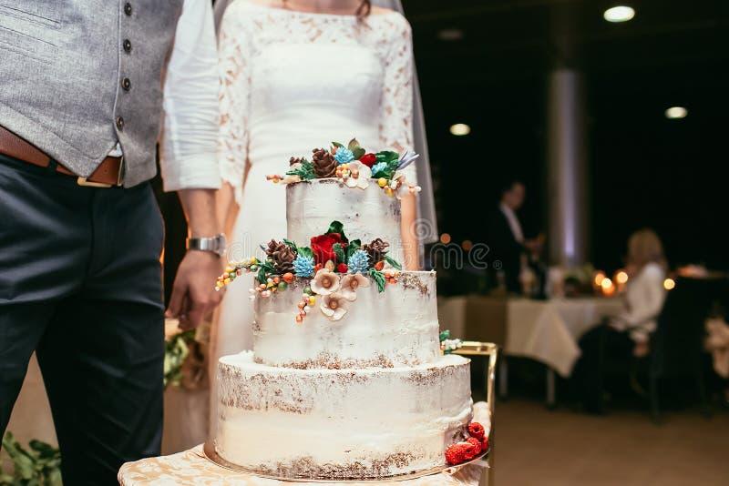 Νύφη και νεόνυμφος με το αγροτικό γαμήλιο κέικ στο γαμήλιο συμπόσιο με στοκ εικόνα με δικαίωμα ελεύθερης χρήσης