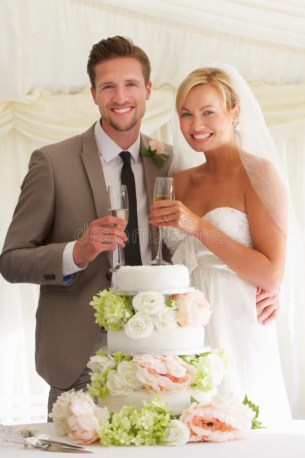 Νύφη και νεόνυμφος με το κέικ που πίνουν CHAMPAGNE στην υποδοχή στοκ εικόνες