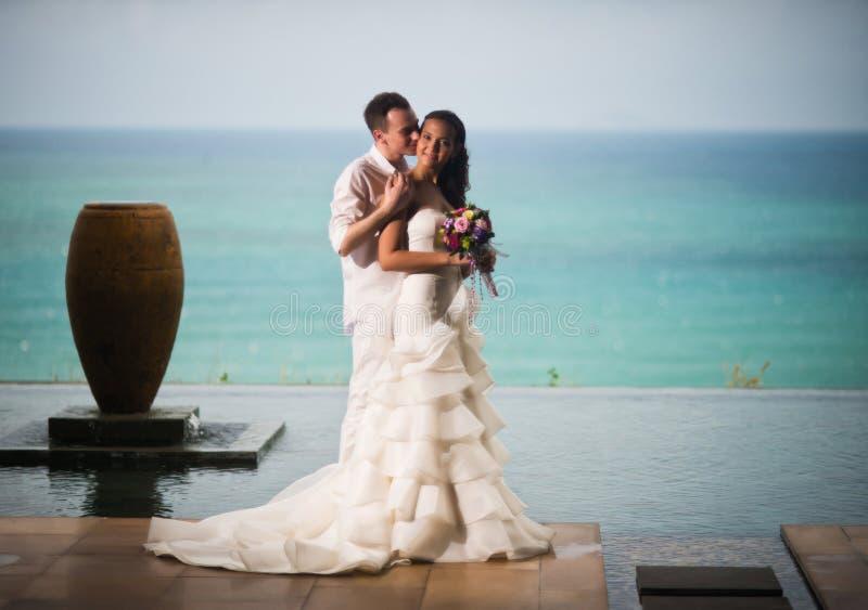 Νύφη και νεόνυμφος που αγκαλιάζουν και που φιλούν ενάντια στη θάλασσα στοκ φωτογραφίες