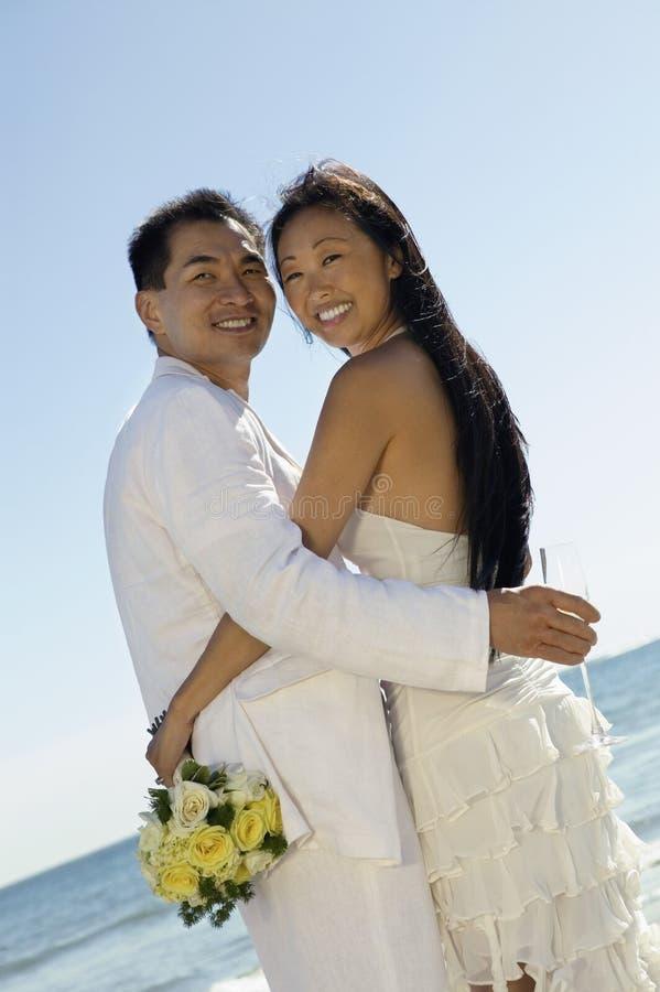 Νύφη και νεόνυμφος που αγκαλιάζουν στην παραλία (πορτρέτο) στοκ φωτογραφίες
