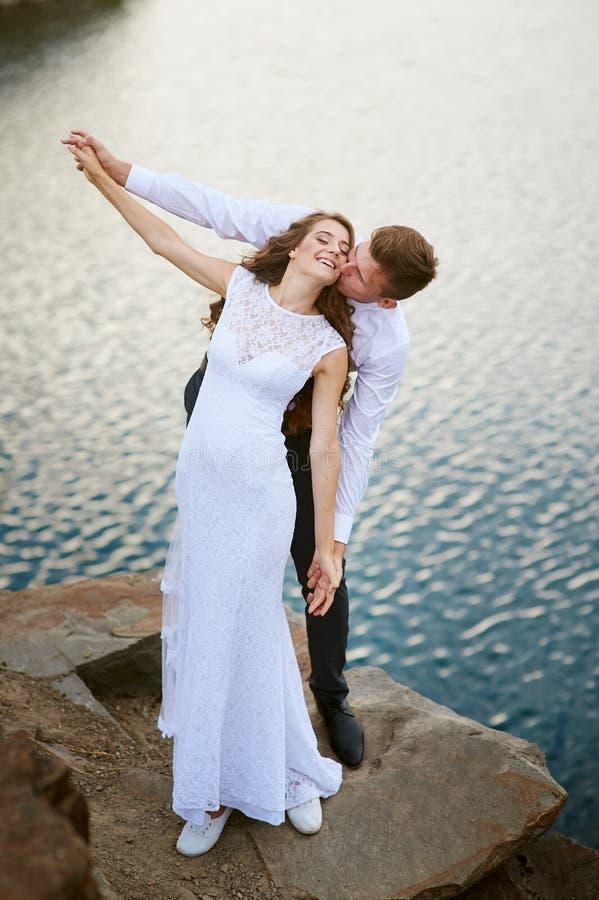 Νύφη και νεόνυμφος που αγκαλιάζουν στο υπόβαθρο του νερού στοκ εικόνες