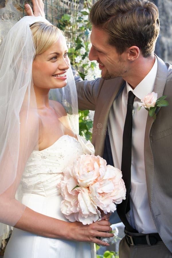Νύφη και νεόνυμφος που αγκαλιάζουν υπαίθρια στοκ φωτογραφία με δικαίωμα ελεύθερης χρήσης