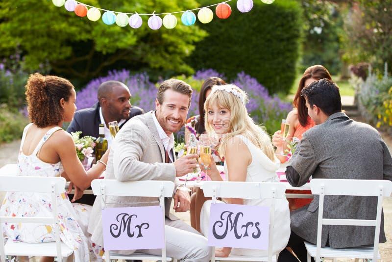 Νύφη και νεόνυμφος που απολαμβάνουν το γεύμα στη δεξίωση γάμου στοκ εικόνα με δικαίωμα ελεύθερης χρήσης