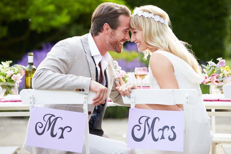 Νύφη και νεόνυμφος που απολαμβάνουν το γεύμα στη δεξίωση γάμου στοκ εικόνα