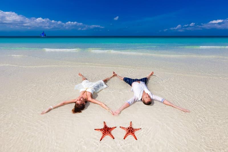 Νύφη και νεόνυμφος που βρίσκονται στην ακτή παραλιών με τον αστερία δύο στοκ φωτογραφία