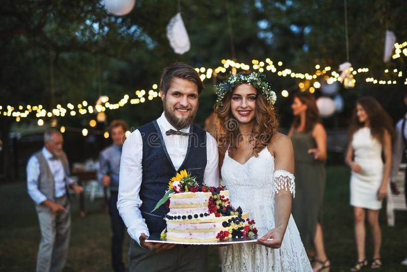 Νύφη και νεόνυμφος που κρατούν ένα κέικ στη δεξίωση γάμου έξω στο κατώφλι στοκ εικόνα