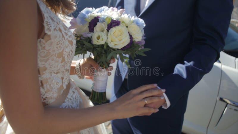 Νύφη και νεόνυμφος που κρατούν τη ζωηρόχρωμη γαμήλια ανθοδέσμη έννοια γάμου Όμορφο νέο γαμήλιο ζεύγος έξω στη φύση στοκ φωτογραφία με δικαίωμα ελεύθερης χρήσης