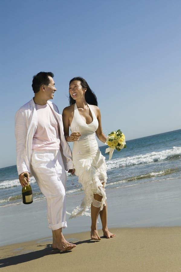 Νύφη και νεόνυμφος που περπατούν στην παραλία στοκ εικόνα με δικαίωμα ελεύθερης χρήσης
