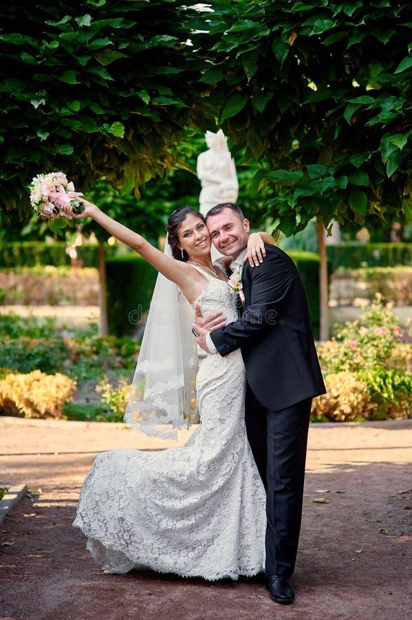 Νύφη και νεόνυμφος που περπατούν στο πάρκο στη ημέρα γάμου τους στοκ φωτογραφίες