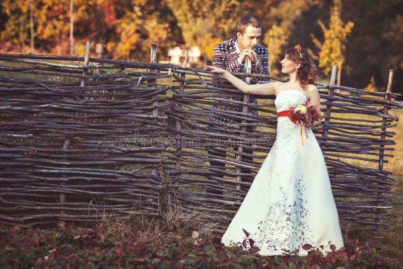 Νύφη και νεόνυμφος που στέκονται κοντά στον ψάθινο φράκτη στοκ φωτογραφία με δικαίωμα ελεύθερης χρήσης