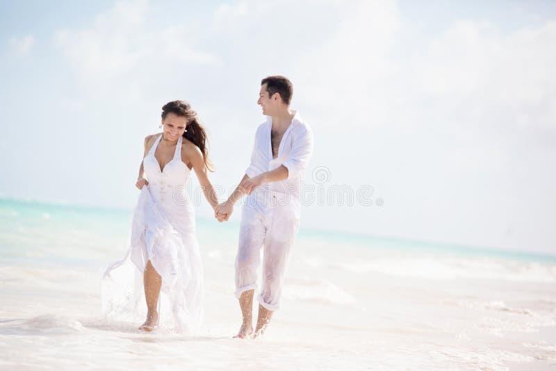 Νύφη και νεόνυμφος που τρέχουν σε μια τροπική παραλία στοκ εικόνα