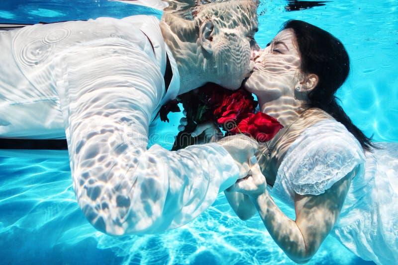 Νύφη και νεόνυμφος που φιλούν τα υποβρύχια κόκκινα λουλούδια γαμήλιας κατάδυσης στοκ εικόνες