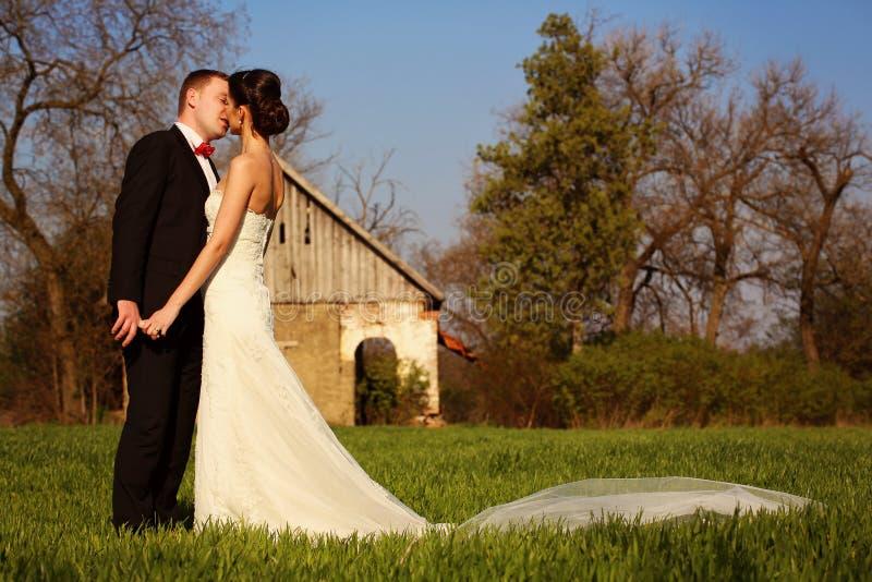 Νύφη και νεόνυμφος σε μια ηλιόλουστη ημέρα αρχειοθετημένη με ένα σπίτι στο υπόβαθρο στοκ φωτογραφία