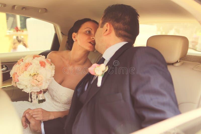 Νύφη και νεόνυμφος στο γαμήλιο αυτοκίνητο στοκ εικόνα με δικαίωμα ελεύθερης χρήσης