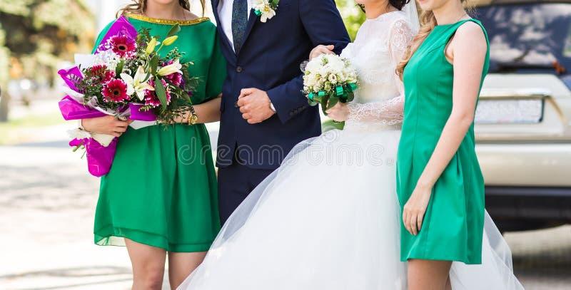 Νύφη και οι παράνυμφοί της που φορούν τα ανοικτό πράσινο φορέματα παράνυμφων στοκ φωτογραφία