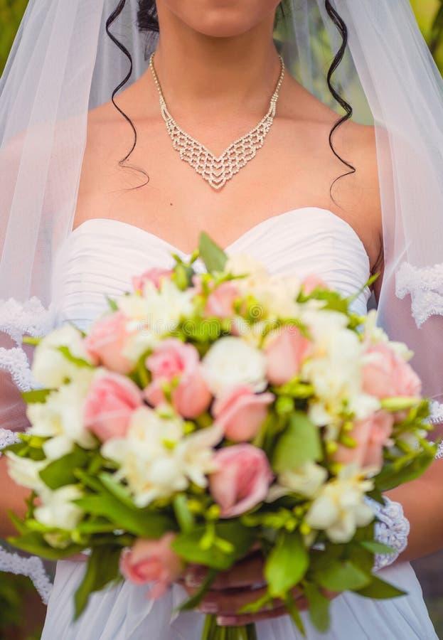 Νύφη με ένα βραχιόλι γύρω από τα λουλούδια εκμετάλλευσης λαιμών στοκ φωτογραφία