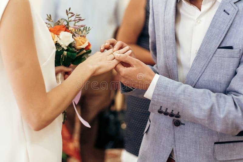 Νύφη με την ανθοδέσμη και νεόνυμφος που ανταλλάσσει τα γαμήλια δαχτυλίδια στο γάμο στοκ εικόνα