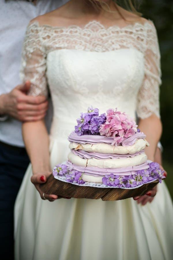 Νύφη με το νόστιμο πορφυρό γαμήλιο κέικ στοκ εικόνες