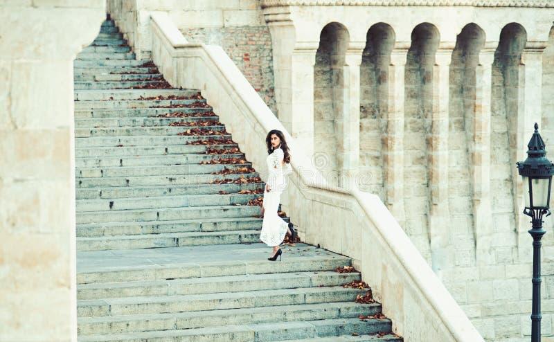 Νύφη μόδας στο άσπρο γαμήλιο φόρεμα στη σκάλα Πρότυπο μόδας με μακρυμάλλη στα βήματα σκαλοπατιών, γάμος στοκ εικόνες