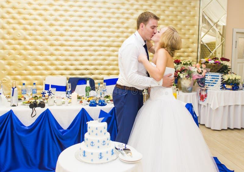 Νύφη ομορφιάς και όμορφος νεόνυμφος με το γαμήλιο κέικ στοκ εικόνα
