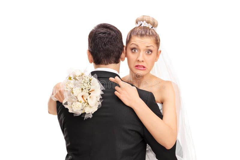 Νύφη που αγκαλιάζει το σύζυγό της με τα δάχτυλά της που διασχίζονται στοκ φωτογραφίες