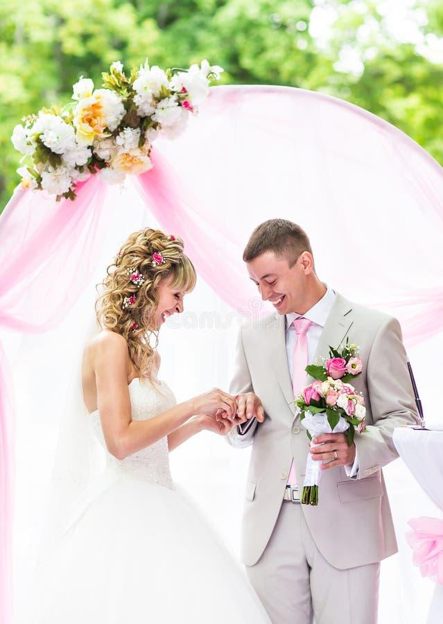Νύφη που βάζει ένα δαχτυλίδι στο δάχτυλο του νεόνυμφου κατά τη διάρκεια της γαμήλιας τελετής στοκ εικόνες