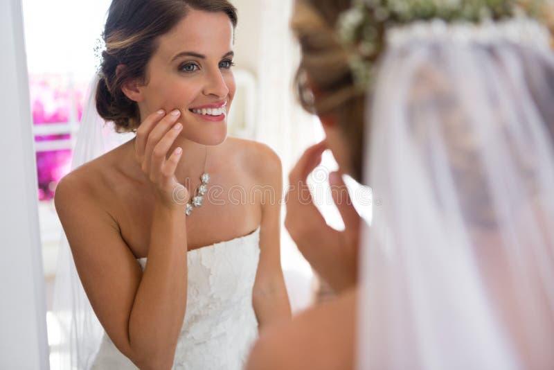 Νύφη που εξετάζει τον καθρέφτη στεμένος στο δωμάτιο συναρμολογήσεων στοκ εικόνα με δικαίωμα ελεύθερης χρήσης